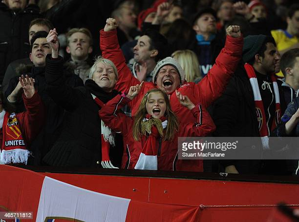 Arsenal fans celebrsate after the FA Cup Quarter Final between Manchester United and Arsenal at Old Trafford on March 9 2015 in Manchester England