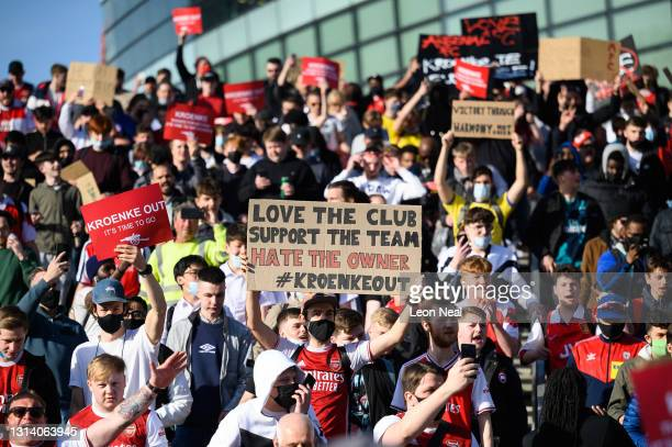 Arsenal fans chant and hold placards during a protest against the club's owner Stan Kroenke ahead of the Premier League match between Arsenal and...