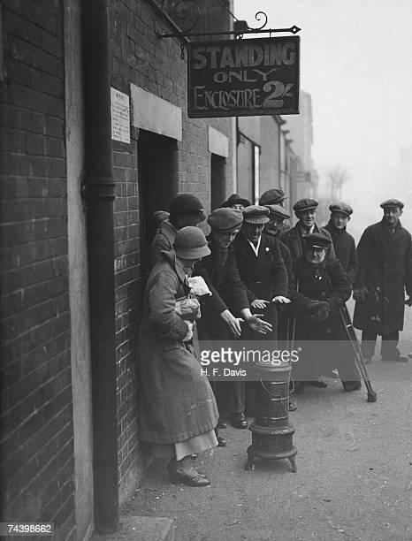 Arsenal fans getting warm from a stove while queuing at the Highbury stadium for tickets to see the match against Chelsea and the ceremony to open...