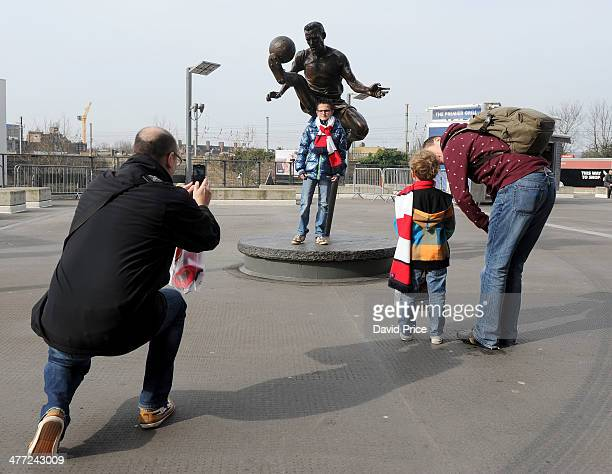 Arsenal fans have their picture taken with the Dennis Bergkamp statue before the FA Cup 6th Round match between Arsenal and Everton at Emirates...