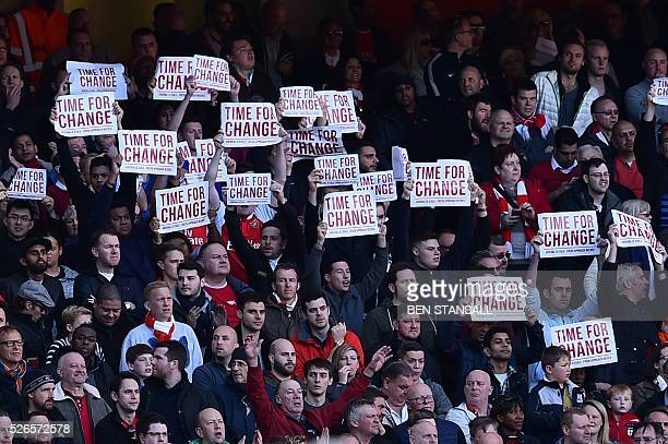 Arsenal fans hold up signs calling for change and a fresh approach at the football club during the English Premier League football match between...