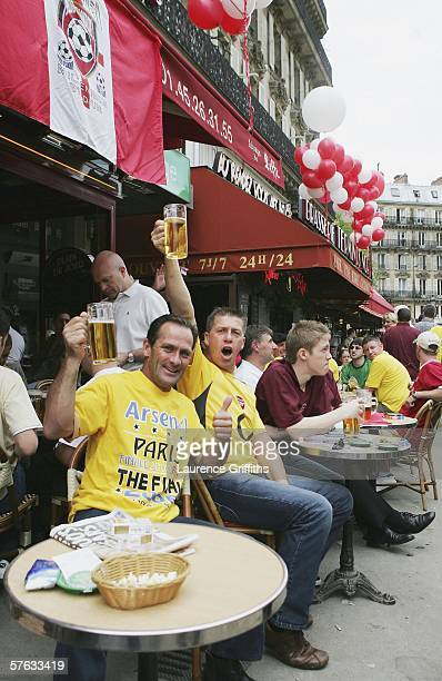 Arsenal fans hold up their glasses of beer at a cafe near the Gare du Nord railway station after arriving for the UEFA Champions League Final against...