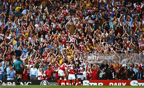 Arsenal Fans in the North Bank celebrate the second of Ian Wright two goals as a lone Everton fan looks on during the FA Premier League match between...