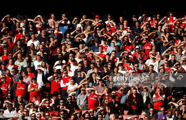 Arsenal fans shade their eyes from the sun during the Premier League match between Arsenal FC and Watford FC at Emirates Stadium on September 29 2018...