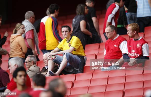 Arsenal fans sit dejected in the stands after the final whistle