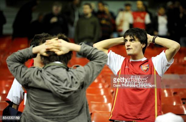 Arsenal fans stand dejected after the final whistle
