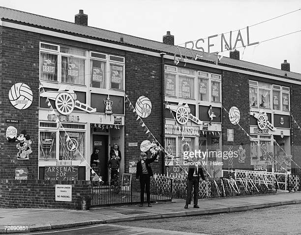 Arsenal fans standing outside their houses in Fife Street Islington which have been decorated to show support for Arsenal in the F A Cup final...