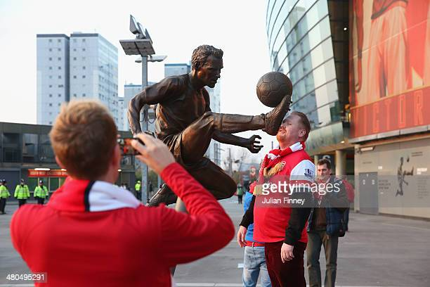 Arsenal fans take photographs by the Dennis Bergkamp statue ahead of the Barclays Premier League match between Arsenal and Swansea City at Emirates...