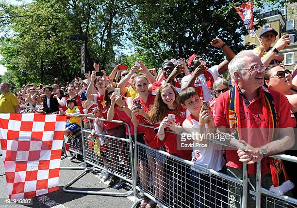 Arsenal fans watch the team on the trophy parade the FA Cup through the streets of Islington on May 18 2014 in London England