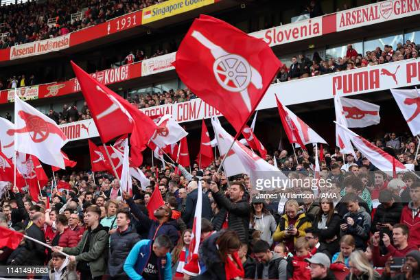 Arsenal fans waving flags during the Premier League match between Arsenal FC and Brighton Hove Albion at Emirates Stadium on May 5 2019 in London...