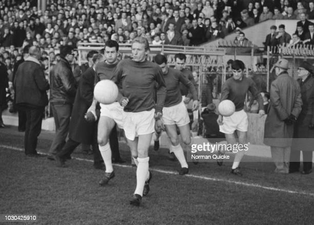 Scottish soccer player Denis Law of Manchester United FC taking the field with his teammates at Arsenal Stadium London UK 28th November 1964
