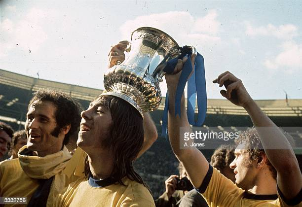 Arsenal Football Club player Charlie George stands between George Graham and a fellow player who are holding the FA Cup on his head