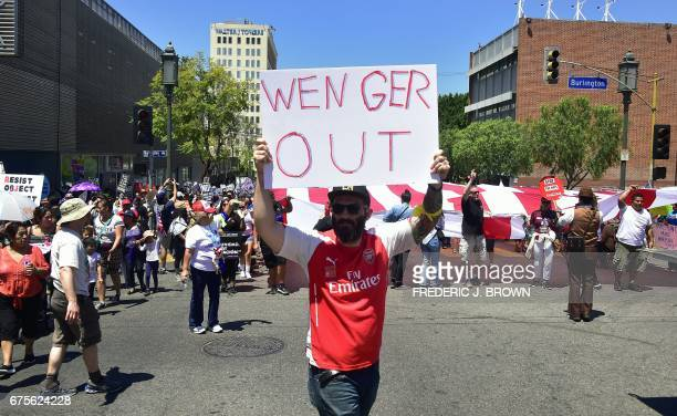 Arsenal football fan Mark Torres carriers his 'Wenger Out' protest placard joining protesters marching on May Day through downtown Los Angeles...