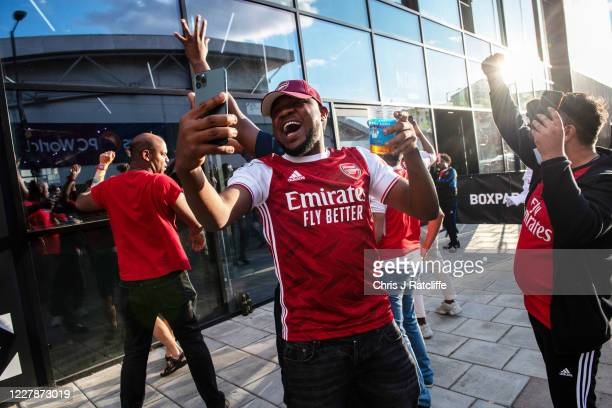 Arsenal Football fans celebrate outside Boxpark Wembley as they watch the match from the street through the window as Arsenal wins the FA Cup at...