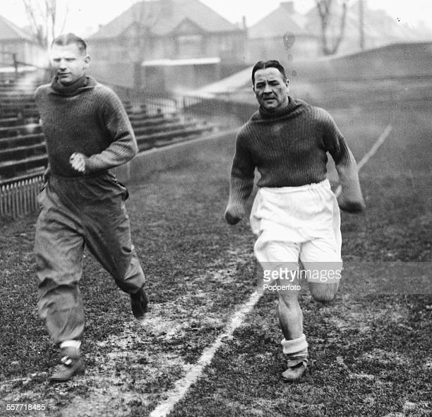 Arsenal football players Alex James and Cliff Bastin running through the mud during training for the upcoming cuptie in Brighton England circa 1935