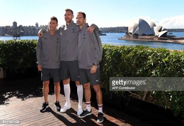 Arsenal football players Laurent Koscielny Per Mertesacker and Petr Cech pose for photos in front of the Sydney Opera House on July 11 ahead of two...