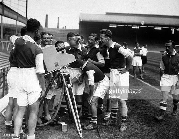 Arsenal Football team peering into a camera at Highbury after playing in the first football match to be filmed live on television, Arsenal vs Arsenal...