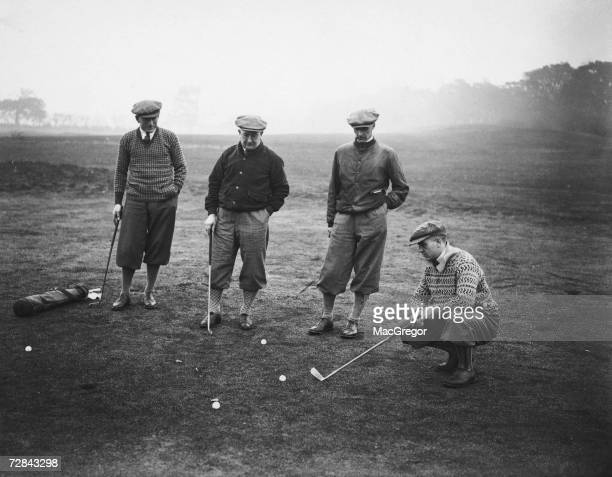 Arsenal footballer Alex James considers his putt during a team training day at a golf course in Hatch End 14th November 1929 Team mate Tom Parker...