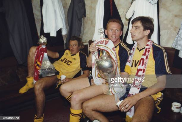 Arsenal footballers from left Paul Merson Perry Groves and Alan Smith celebrate in their dressing room with the League trophy and the Barclays First...