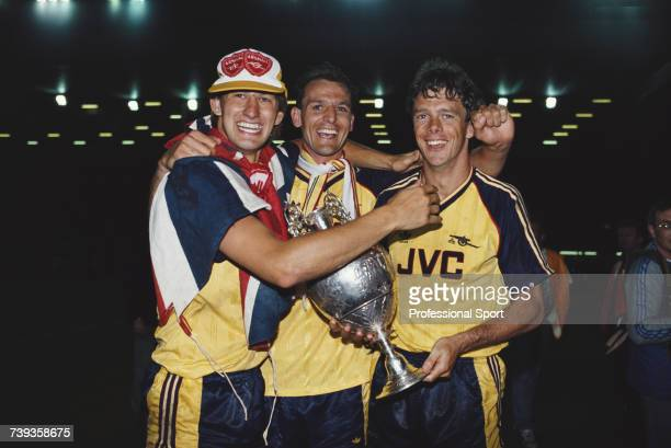 Arsenal footballers from left Tony Adams Steve Bould and David O'Leary celebrate with the League trophy after beating Liverpool FC 20 away at Anfield...