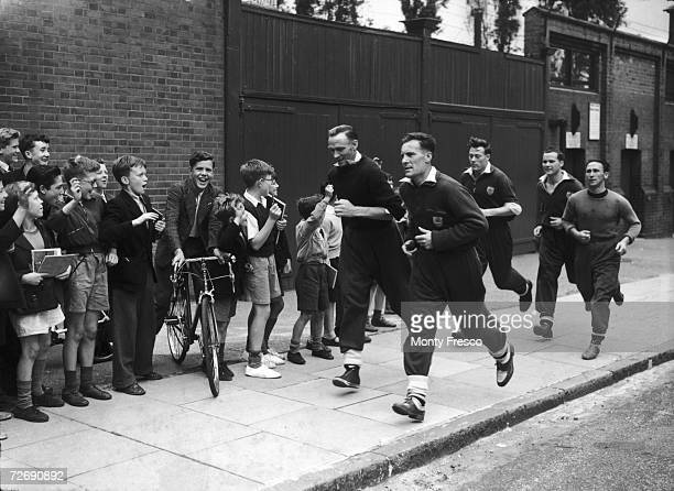 Arsenal footballers including Lionel Smith Don Roper and Jack Kelsey running on the streets around the club's Highbury stadium in preparation for the...