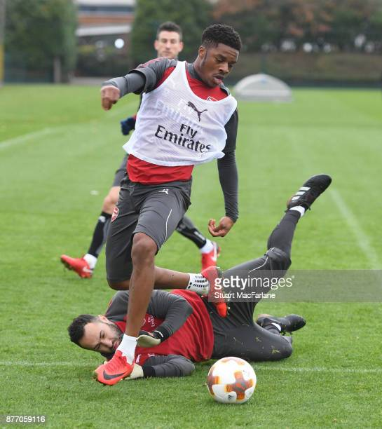 Arsenal goalkeeper David Ospina saves at the feet of Chuba Akpom during a training session at London Colney on November 21 2017 in St Albans England