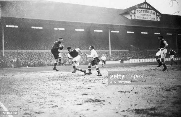Arsenal goalkeeper Frank Moss makes a save from Tottenham striker George Hunt as defender Leslie Compton rushes in during a league match at White...