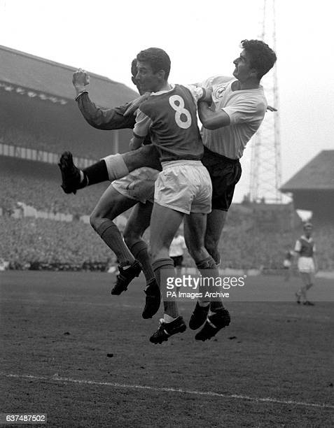 Arsenal goalkeeper Jack McClelland punches the ball clear from Tottenham Hotspur's Maurice Norman and Arsenal teammate Geoff Strong
