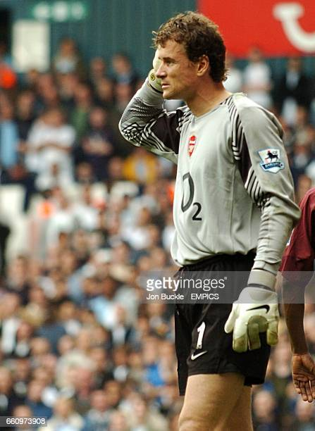 Arsenal goalkeeper Jens Lehmann clutches his head after being struck by an object from the crowd
