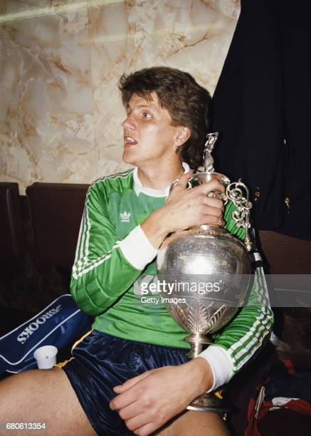 Arsenal goalkeeper John Lukic cradles the trophy after Arsenal had beaten Liverpool 20 to win the First Division Championship at Anfield on May 26...