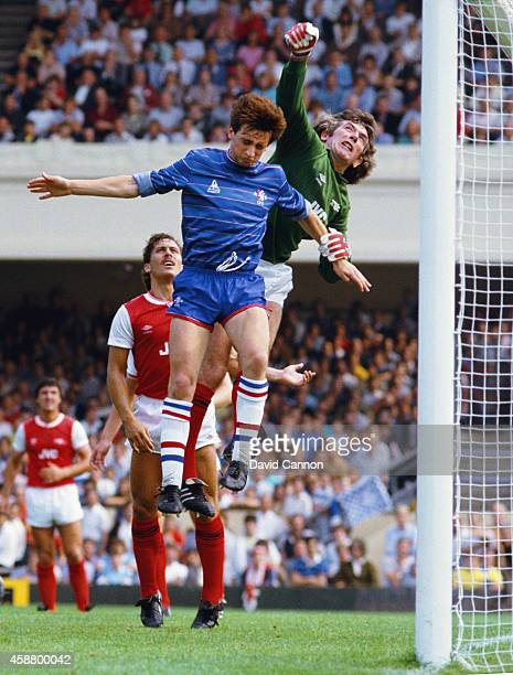 Arsenal goalkeeper Pat Jennings clears from Chelsea winger Pat Nevin as Arsenal defender Kenny Sansom looks on during a League Division One match...