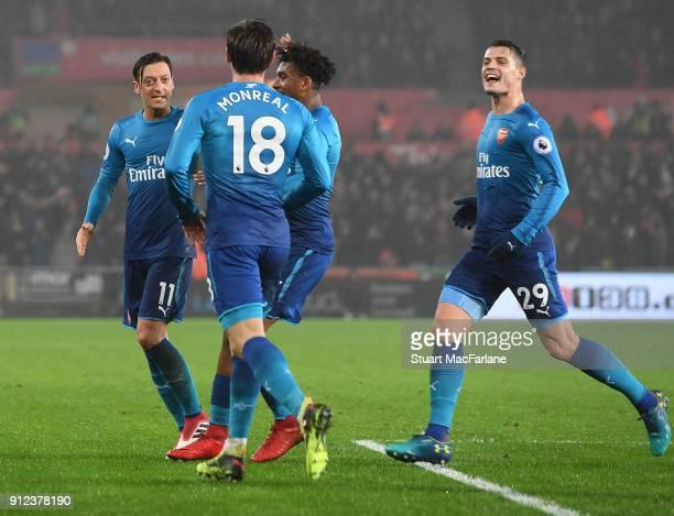 Arsenal goalscorer Nacho Monreal celebrates his goal with Mesut Ozil Alex Iwobi and Granit Xhaka during the Premier League match between Swansea City...