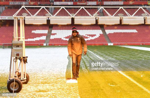 Arsenal groundstaff clear the pitch and terracing of snow before the Premier League match between Arsenal and Manchester City at Emirates Stadium on...
