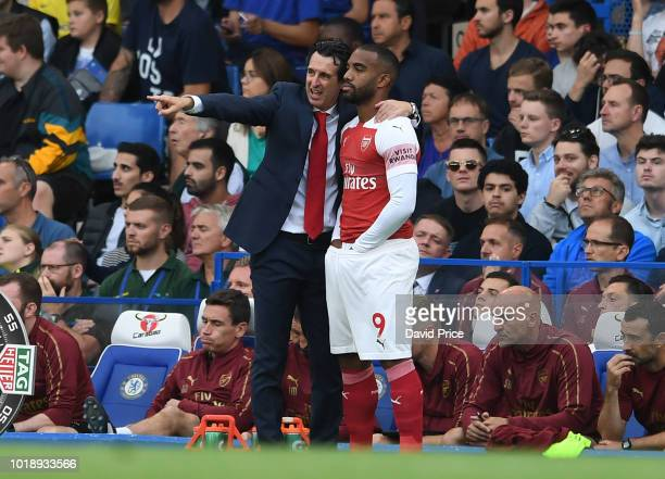 Arsenal Head Coach Unai Emery chats to Alexandre Lacazette as he prepares to come on as a sub during the Premier League match between Chelsea FC and...