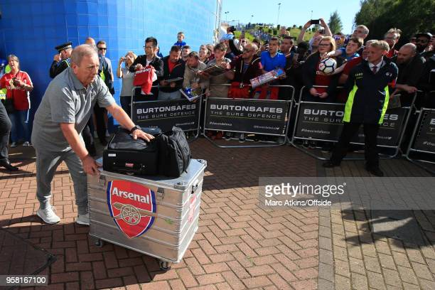 Arsenal kit manager Vic Akers pushes a crate back to the team bus for the final time during the Premier League match between Huddersfield Town and...