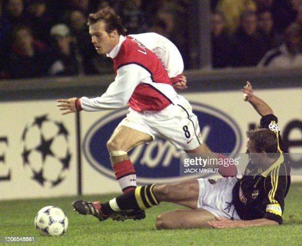 Arsenal London's Fredrik Ljungberg escapes Krister Nordin of AIK Solna in a UEFA Champions League match in Stockholm 02 November 1999