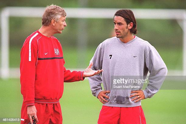 Arsenal manager Arseen Wenger with Robert Pires during a training session at London Colney on September 16 2002 in St Albans England