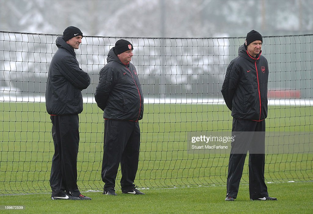 Arsenal manager Arsenal Wenger (R) assistant Steve Bould (L) and 1st team coach Neil Banfield look on during a training session at London Colney on January 22, 2013 in St Albans, England.