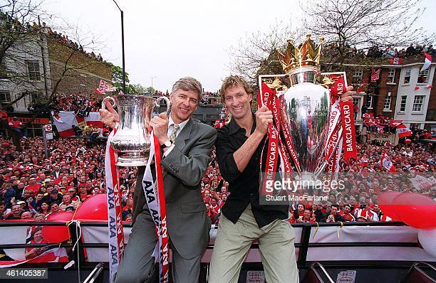 Arsenal manager Arsene Wenger and captain Tony Adams hold the FA Cup and Premiership trophy outside Islington Town Hall on May 12 2002 London England