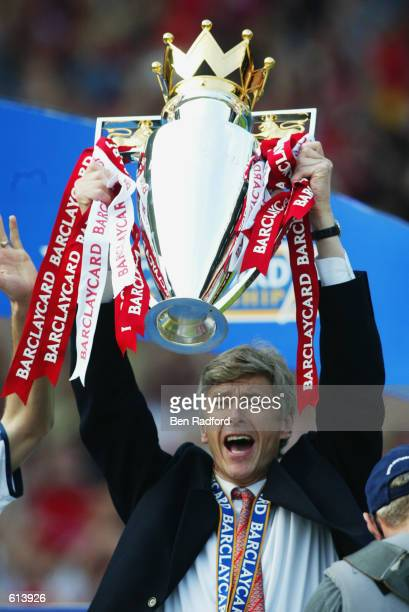 Arsenal manager Arsene Wenger celebrates by lifting the Premiership trophy after the FA Barclaycard Premiership match between Arsenal and Everton...
