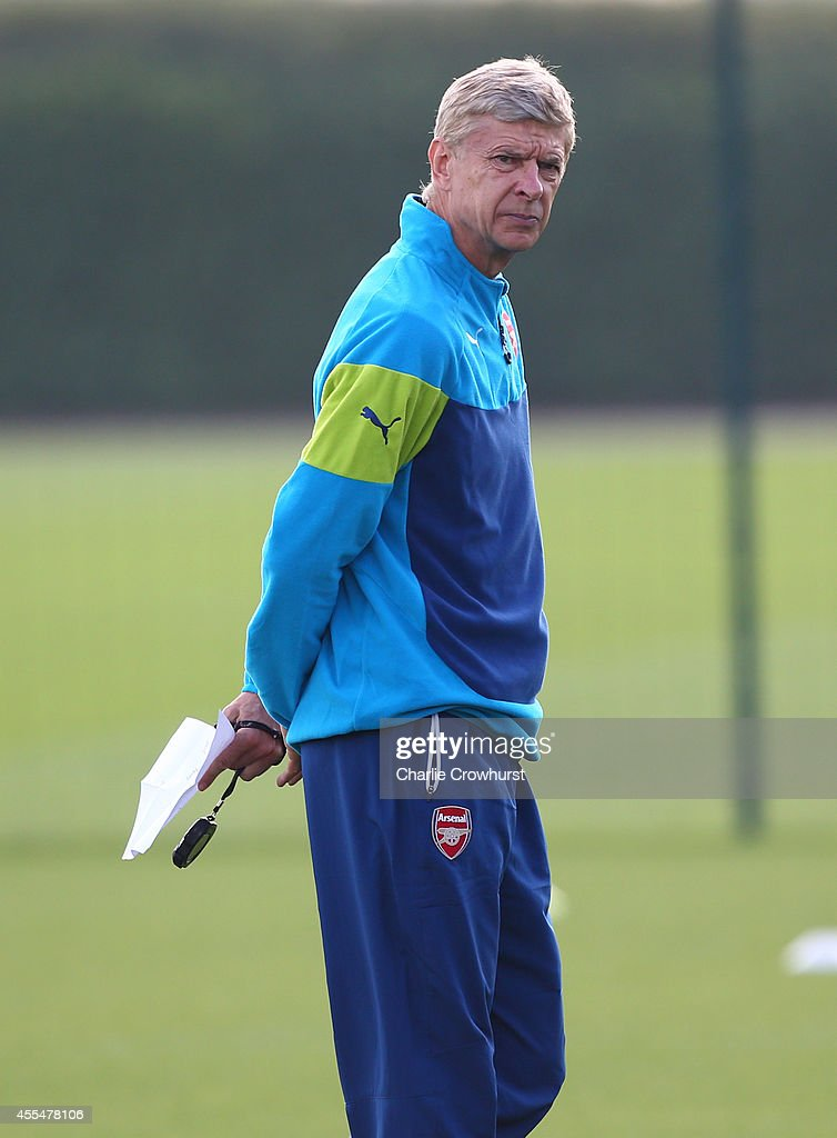 Arsenal manager Arsene Wenger keeps an eye on the session during a Arsenal Training Session ahead of their Champions League fixture against Borussia Dortmund on September 15, 2014 in St Albans, England.