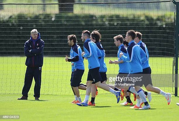 Arsenal manager Arsene Wenger looks on as the squad warm up before a training session at London Colney on May 10 2014 in St Albans England