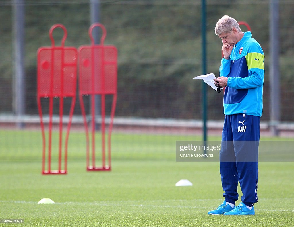 Arsenal manager Arsene Wenger ponders during a Arsenal Training Session ahead of their Champions League fixture against Borussia Dortmund on September 15, 2014 in St Albans, England.