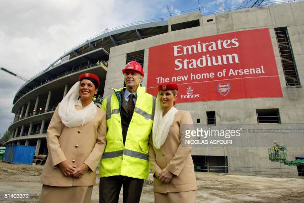 Arsenal manager Arsene Wenger poses with fight attendents from Emirates Airlines in front of Arsenal's new stadium 05 October 2004 in London...