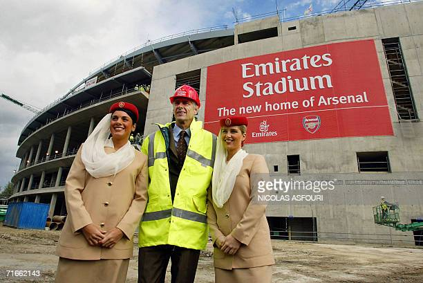 Arsenal manager Arsene Wenger poses with flight attendants from Emirates Airlines in front of Arsenal's new stadium 05 October 2004 in London....