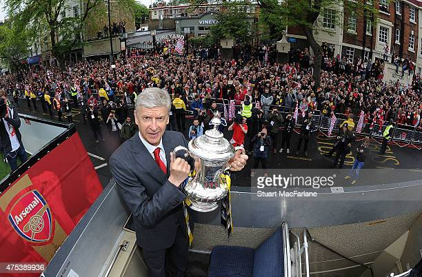 Arsenal manager Arsene Wenger poses with the cup during the Arsenal FA Cup Victory Parade in Islington on May 31 2015 in London England