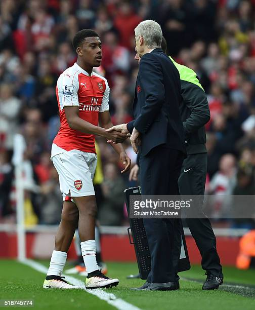 Arsenal manager Arsene Wenger shakes hands with Alex Iwobi after his substitution during the Barclays Premier League match between Arsenal and...