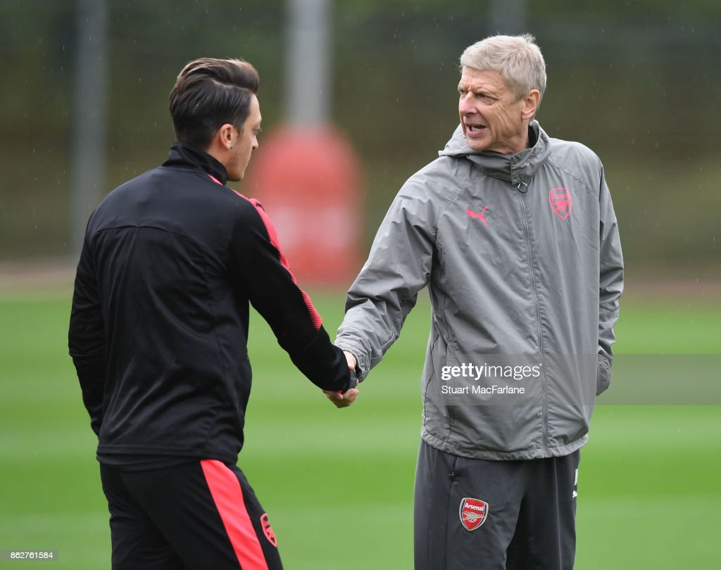 Arsenal manager Arsene Wenger shakes hands with Mesut Ozil before a training session at London Colney on October 18, 2017 in St Albans, England.