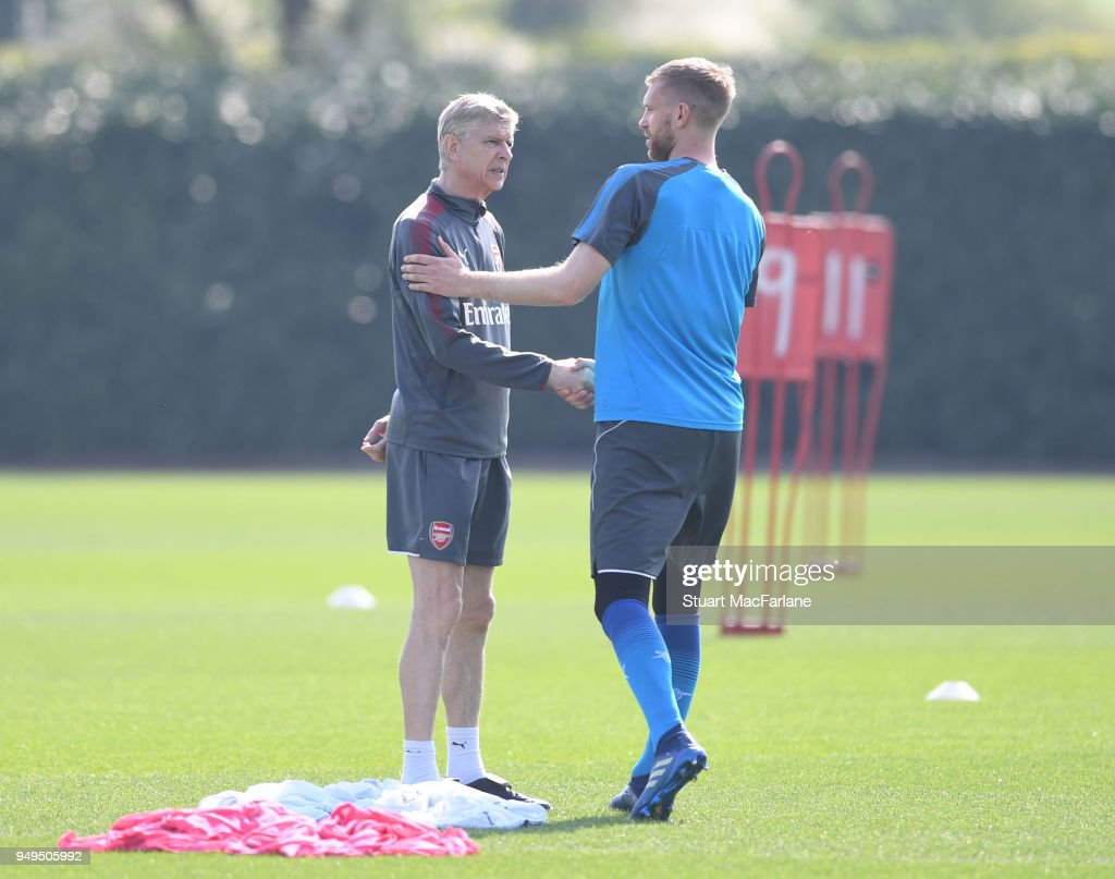 Arsenal manager Arsene Wenger shakes hands with Per Mertesacker before a training session at London Colney on April 21, 2018 in St Albans, England.
