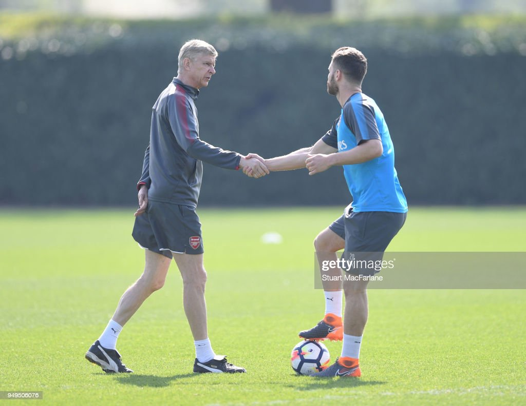 Arsenal manager Arsene Wenger shakes hands with Shkodran Mustafi before a training session at London Colney on April 21, 2018 in St Albans, England.